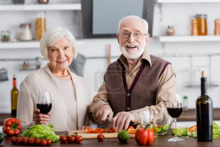 Photo for Happy senior man cutting vegetables near retired wife with glass of wine - Royalty Free Image