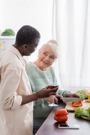 happy senior woman cutting bell pepper near african american husband with glass of wine