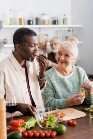 Photo for African american man eating cherry tomato near senior woman and retired friends on blurred background - Royalty Free Image