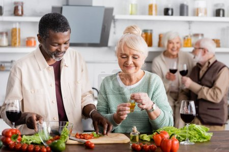 Afrikanischer Mann und glückliche Seniorin beim Zubereiten von Salat in der Nähe pensionierter Freunde auf verschwommenem Hintergrund