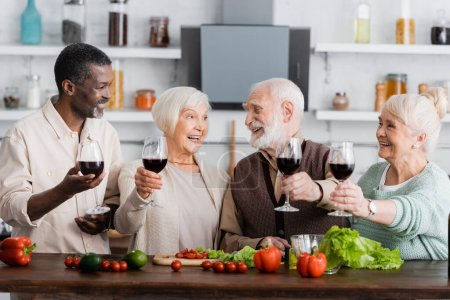 Photo for Joyful multicultural pensioners holding glasses on wine near vegetables on table - Royalty Free Image