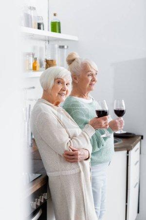szczęśliwe emerytki trzymające kieliszki z winem w kuchni