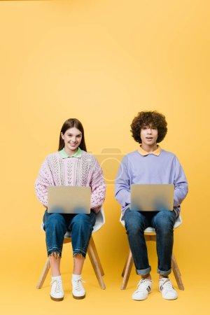 Foto de Adolescentes sonrientes con computadoras portátiles sentados en sillas sobre fondo amarillo - Imagen libre de derechos