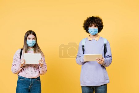 Photo for Teenagers in medical masks holding digital tablets on yellow background - Royalty Free Image