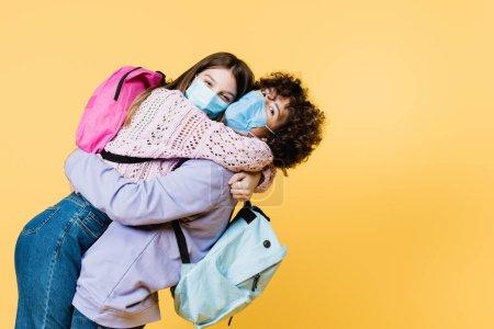 Photo pour Les adolescents dans des masques médicaux et des sacs à dos câlins isolés sur jaune - image libre de droit