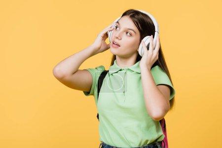Photo pour Adolescent utilisant des écouteurs isolés sur jaune - image libre de droit