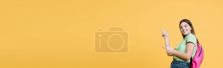 Photo for Positive teenager with backpack pointing with fingers isolated on yellow, banner - Royalty Free Image