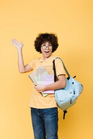 Photo pour Adolescent joyeux avec cahiers et sac à dos pointant avec la main isolé sur jaune - image libre de droit