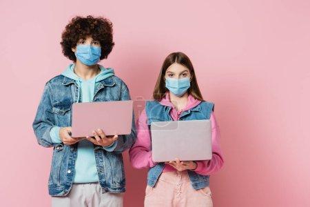 Photo pour Les adolescents dans des masques médicaux regardant la caméra tout en tenant des ordinateurs portables sur fond rose - image libre de droit