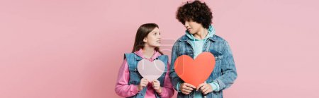 Smiling teenager holding paper heart and looking at boyfriend isolated on pink, banner