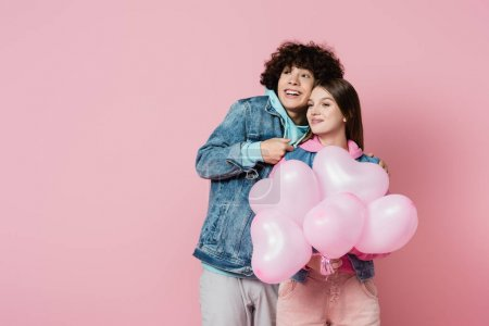 Cheerful teenager sanding near girlfriend with balloons isolated on pink