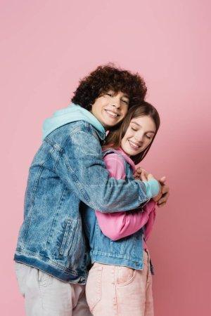 Photo pour Vue latérale de l'adolescent bouclé embrassant petite amie sur fond rose - image libre de droit