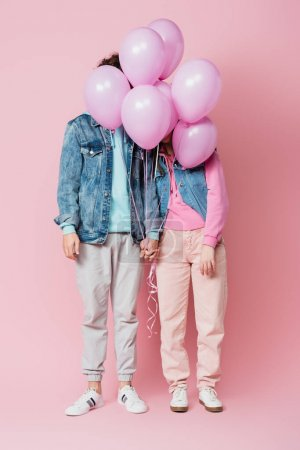 Teen couple holding hands while balloons covering faces on pink background