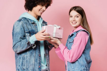 Smiling teenager giving present to girlfriend on pink background