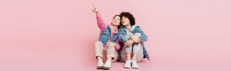Photo for Smiling teenager pointing with finger while sitting near boyfriend on pink background, banner - Royalty Free Image