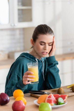 femme mécontente toucher la tête tout en tenant un verre de jus près de fruits frais dans la cuisine