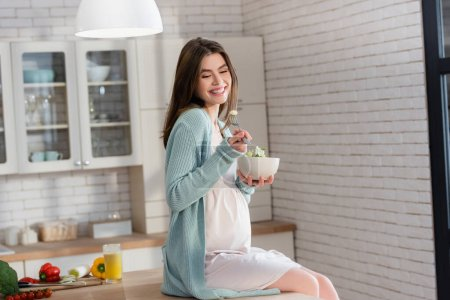 Photo for Joyful pregnant woman eating vegetable salad while sitting on kitchen counter - Royalty Free Image