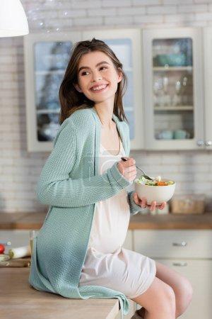 Schwangere hält Schüssel mit Gemüsesalat auf Küchentisch