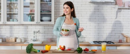 happy pregnant woman eating fresh vegetable salad in modern kitchen, banner