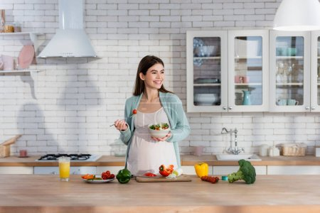 cheerful pregnant woman eating fresh vegetable salad in modern kitchen