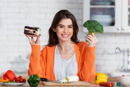 Photo pour Femme gaie choisir entre gâteau et brocoli frais tout en souriant à la caméra - image libre de droit