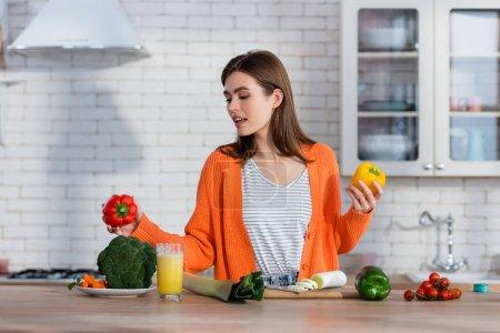 Photo pour Jeune femme tenant poivron frais près des légumes et du jus sur le comptoir de la cuisine - image libre de droit