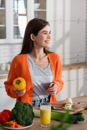 Photo for Smiling woman looking away while holding bell pepper near fresh vegetables and juice on blurred foreground - Royalty Free Image