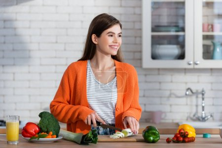 joyful woman looking away while cutting fresh leek near vegetables on table