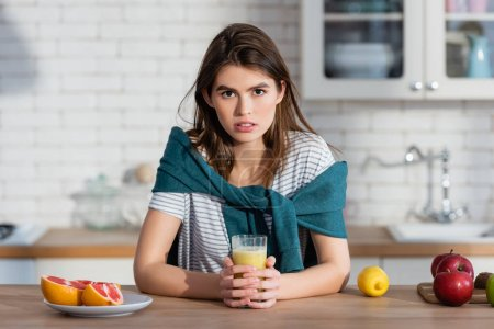 young woman looking at camera near glass of juice and fresh fruits in kitchen