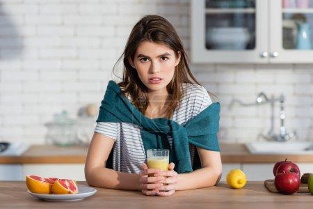 Photo pour Jeune femme regardant la caméra près du verre de jus et de fruits frais dans la cuisine - image libre de droit