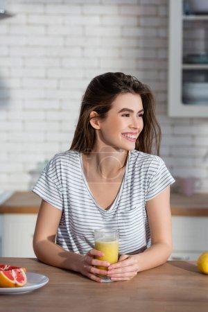 glückliche Frau schaut in der Nähe von Glas mit frischem Saft weg und schneidet Grapefruit in der Küche