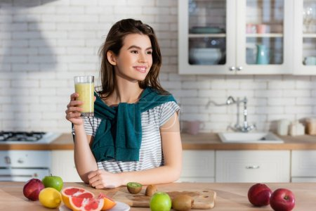 smiling woman holding fresh juice near fruits on kitchen table