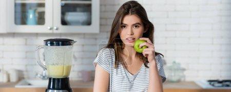 Photo pour Jeune femme tenant pomme mûre près du mélangeur avec smoothie frais, bannière - image libre de droit