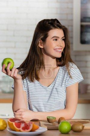 mujer complacida sosteniendo manzana madura cerca de frutas frescas en la cocina