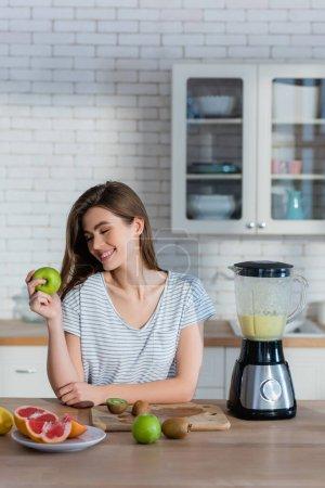 Frau hält reifen Apfel in der Nähe von Früchten und Mixer in Küche