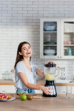 Photo pour Rire femme regardant caméra tout en préparant smoothie aux fruits dans la cuisine - image libre de droit