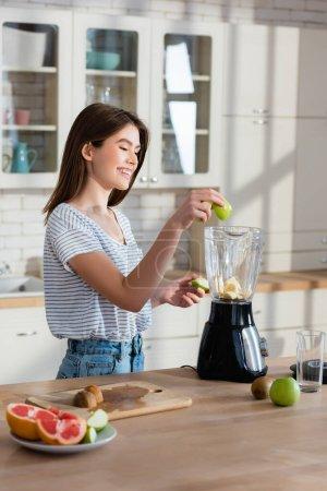 freudige Frau fügt Apfel im Mixer hinzu, während sie das Frühstück in der Küche zubereitet