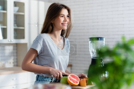 glückliche Frau schneidet frisches Obst beim Zubereiten des Frühstücks im unscharfen Vordergrund