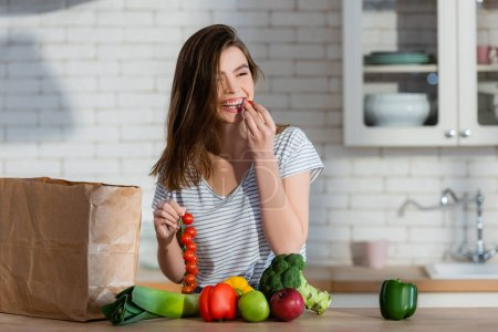 laughing woman eating cherry tomato near apples and fresh vegetables in kitchen