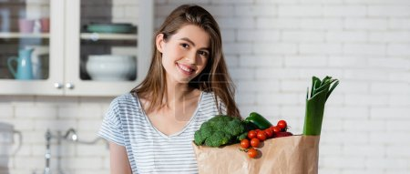 Photo for Joyful woman looking at camera near fresh vegetables in paper bag, banner - Royalty Free Image