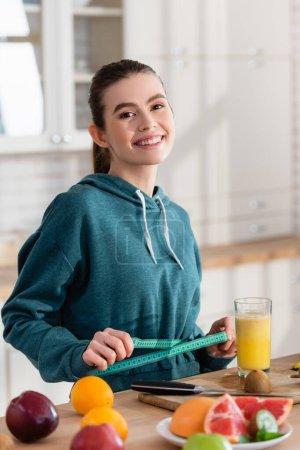 Foto de Mujer feliz mirando a la cámara mientras mide la cintura cerca de frutas frescas - Imagen libre de derechos