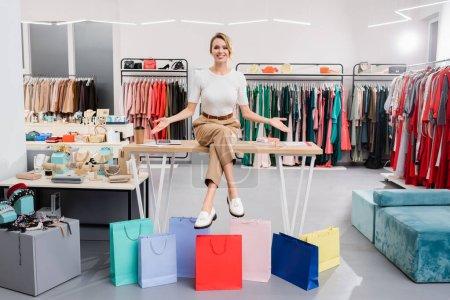 Photo pour Vendeur souriant pointant vers les sacs à provisions tout en étant assis sur la table dans le showroom - image libre de droit