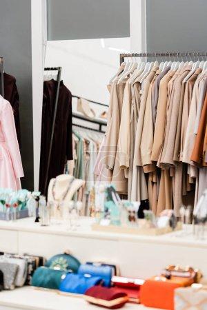 Photo pour Vêtements sur cintres près des accessoires au premier plan flou dans le showroom - image libre de droit