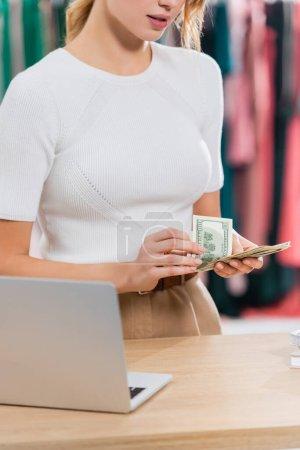 Vue recadrée du vendeur tenant des dollars près d'un ordinateur portable sur le premier plan flou dans la salle d'exposition