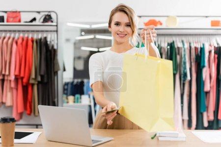 Photo pour Joyeux vendeur tenant sac à provisions et de l'argent dans le showroom - image libre de droit