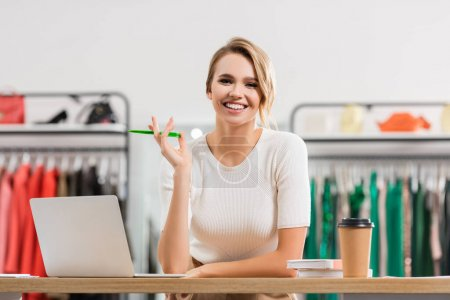 Positive seller holding pen near laptop and coffee to go in showroom