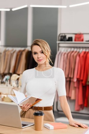 Blonde seller with notebook standing near laptop and coffee to go on table in showroom