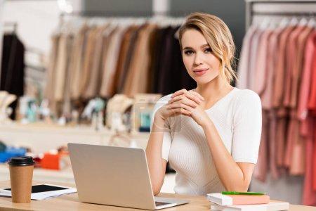 Showroom-Verkäufer blickt auf Kamera in der Nähe von Laptop, Coffee to go und Notebooks