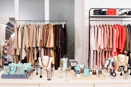 Photo pour Accessoires sur table dans le showroom avec des vêtements sur fond flou - image libre de droit