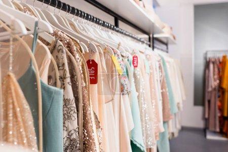 Photo pour Étiquettes de prix avec lettrage de vente sur cintres avec des vêtements à la mode dans le showroom - image libre de droit